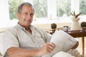 Eye care Bardstown, KY - Man in living room reading newspaper smiling